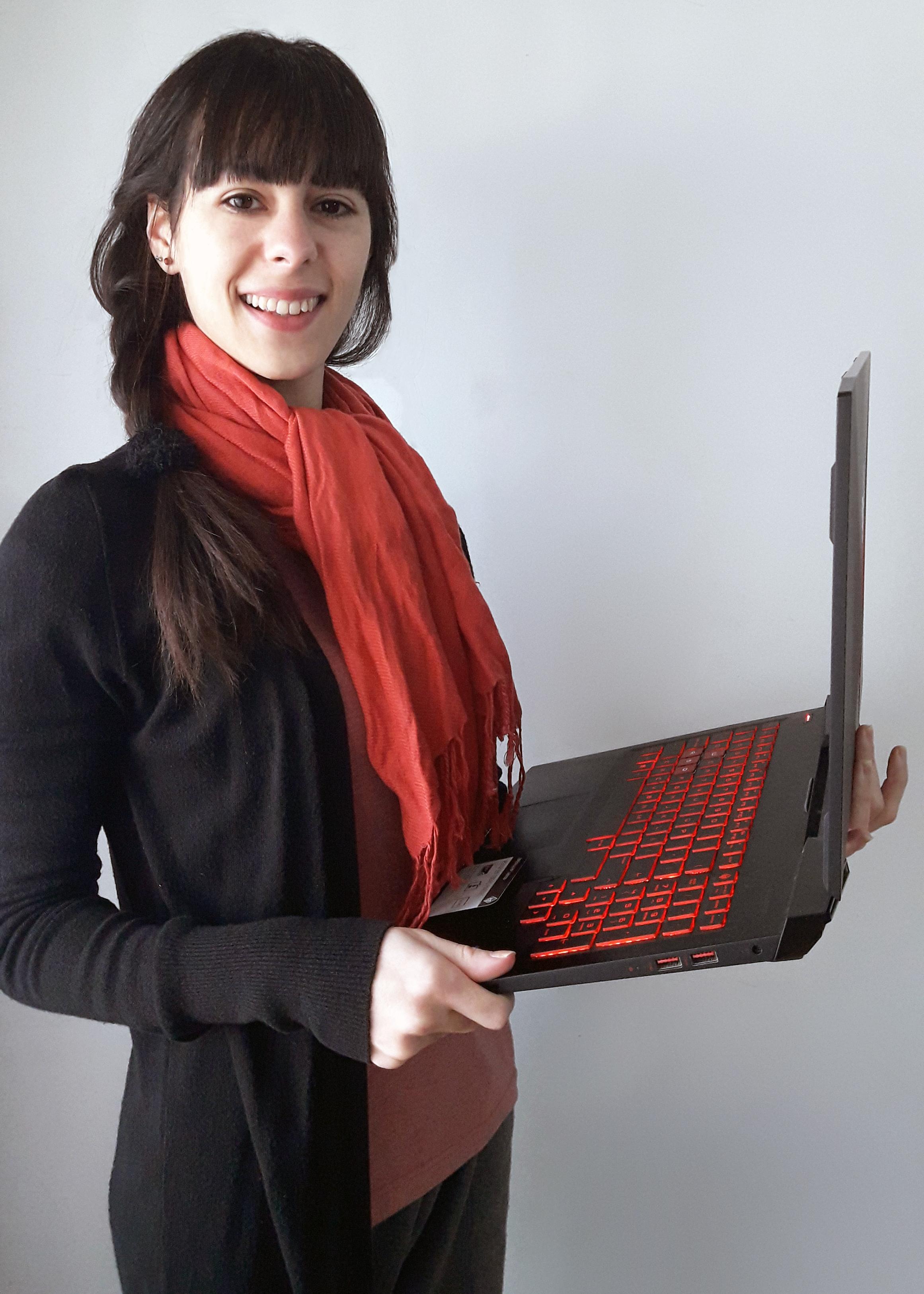 fotografía de Valeria García, mujer joven sosteniendo una notebook y sonriendo a la cámara